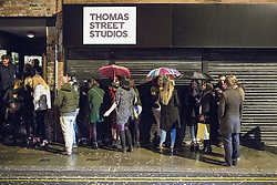 "© Licensed to London News Pictures . 19/12/2014 . Manchester , UK . People queue beneath umbrellas as they wait to enter a club on Thomas Street . "" Mad Friday "" revellers out in the rain and cold in Manchester . Mad Friday is typically the busiest day of the year for emergency services , taking place on the last Friday before Christmas when office Christmas parties and Christmas revellers enjoy a night out .  Photo credit : Joel Goodman/LNP"