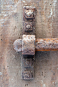 detail of an old rusty metal bold on wooden door