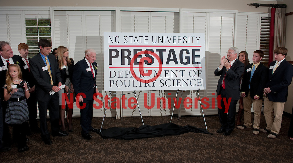 Chancellor Woodson, right, and Bill Prestage, left, unveil the new logo for the Prestage Department of Poultry Science. Photo by Marc Hall/NC State