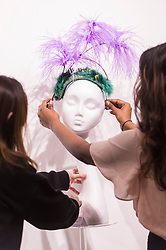 "© Licensed to London News Pictures. 05/04/2019. LONDON, UK. Gallery assistants check a creation at ""The Great Hat Exhibition - World Garden"", which is taking place at the Menier Gallery near London Bridge until 12 April 2019, as part of London Hat Week.  150 international milliners have created 200 hats inspired by the colours, flowers, plants and landscapes from around the world.  The exhibition is curated by Monique Lee Millinery and supported by X Terrace, a fashion platform.  Photo credit: Stephen Chung/LNP"