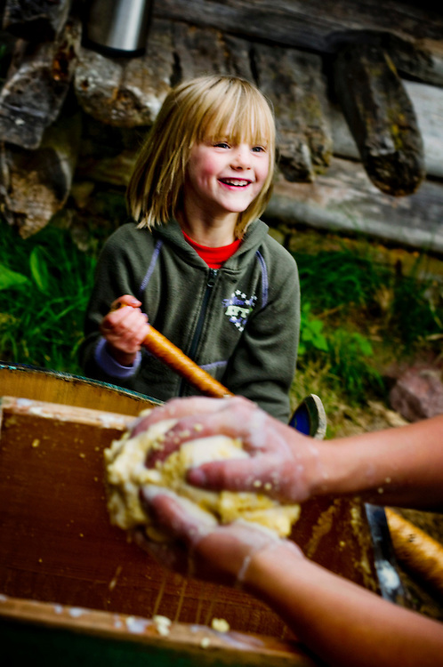 "Evelina Axelsson, 6,  helping her mother Anna as she makes butter. They live with their family on a  ""Fäbod"" in the forests outside Älvdalen, Dalarna, Sweden...Photographer: Chris Maluszynski /MOMENT"