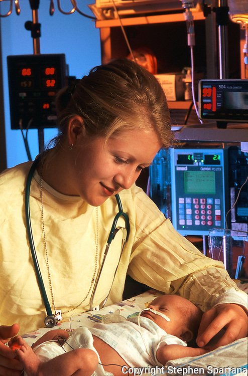 NICU nurse portrait caring for infant taken for brochure cover. Machinery in background.