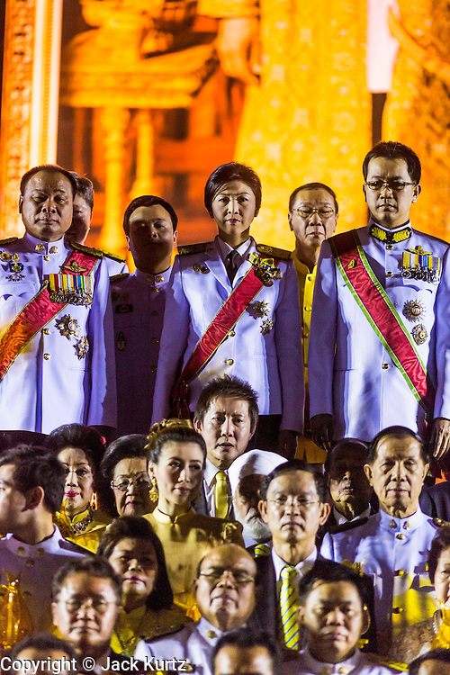 YINGLUCK SHINAWATRA (center) the Prime Minister of Thailand, and ANUSORN AMORNCHAT, her husband, (right) on stage the celebration of the birthday of the King in Bangkok. Thais observed the 86th birthday of Bhumibol Adulyadej, the King of Thailand, their revered King on Thursday. They held candlelight services throughout the country. The political protests that have gripped Bangkok were on hold for the day, although protestors did hold their own observances of the holiday. Thousands of people attended the government celebration of the day on Sanam Luang, the large public space next to the Grand Palace in Bangkok.