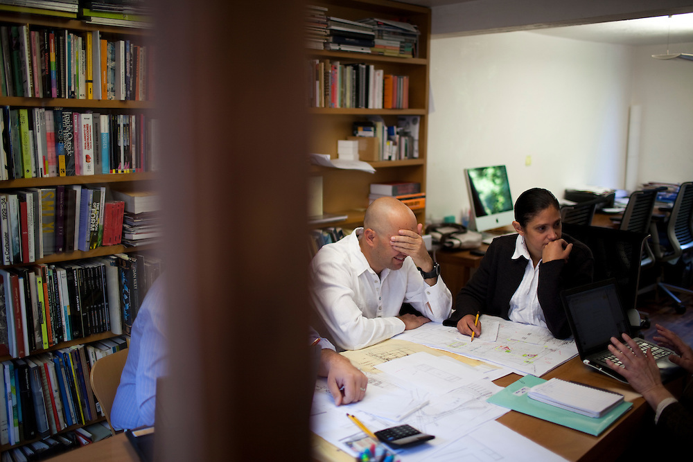 Jose Castillo(hand over face) and Saidee Springall of Arquitectura 911Sc, hold a meeting in their office with consultants from the Theater Project Consultancy about the design for the Guadalajara Performing Arts Center.