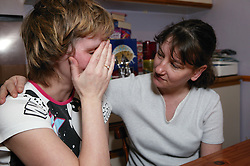 Distressed woman being comforted by her sister,