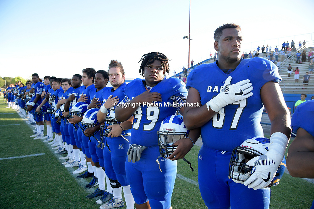 Apopka offensive lineman Will Barnes (67), right, and defensive lineman Boris Lewis (99) stand with teammates for the playing of the national anthem before a spring high school football game against Orange City University in Apopka, Fla., Thursday, May 25, 2017. (Photo by Phelan M. Ebenhack)