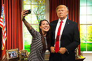 UNITED KINGDOM, London: 18 January 2017 Visitor Helen Smith takes a selfie with the wax figure of President Elect Donald J. Trump in the Madame Tussauds London's Oval Office section at its unveiling today. The London wax figure is one of four Trump figures created by Madame Tussauds globally, the others are in Washington D.C, New York and Orlando. Rick Findler / Story Picture Agency