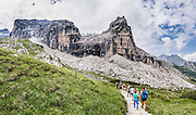 Young people hike towards Torrione di Vallesinella in the Brenta Dolomites. From the ski resort of Madonna di Campiglio in the Trentino-Alto Adige/Südtirol region of Italy, the Passo Groste lift takes you directly into the Brenta Dolomites to enjoy scenic mountain hiking trails. 200 million years ago, Triassic coral reefs fossilized into Dolomite. Collision of tectonic plates lifted the Dolomites within the Southern Limestone Alps. UNESCO honored the Dolomites as a natural World Heritage Site in 2009. This panorama was stitched from 4 overlapping photos.