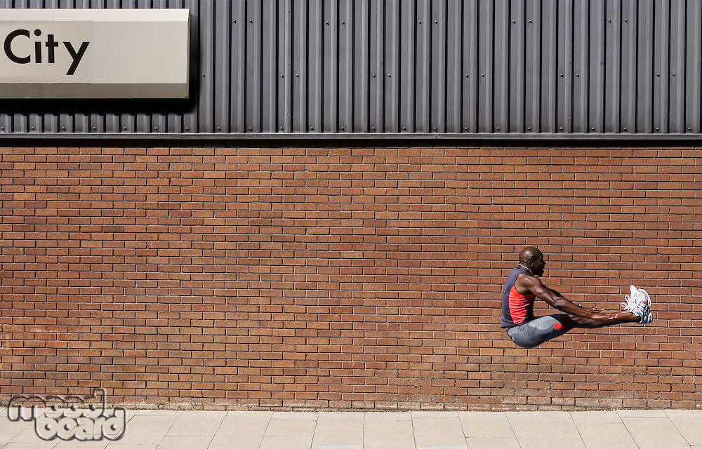Man jumping by wall with 'city' written on it
