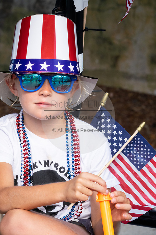 A young boy wearing patriotic clothes rides on the back of a golf cart float during the annual Independence Day parade July 4, 2019 in Sullivan's Island, South Carolina. The tiny Sea Island beach community across from Charleston, was once a quarantine station for enslaved Africans, and is now one of the most affluent, least diverse communities with one of highest per capita real estate costs in the United States.