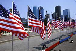American flags waving in front of the Houston, Texas skyline on Independence Day.