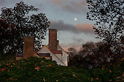 Boxwoods on the West side of the St. George Tucker House with full moon at sunset. Fall stock in Colonial Williamsburg's Historic Area