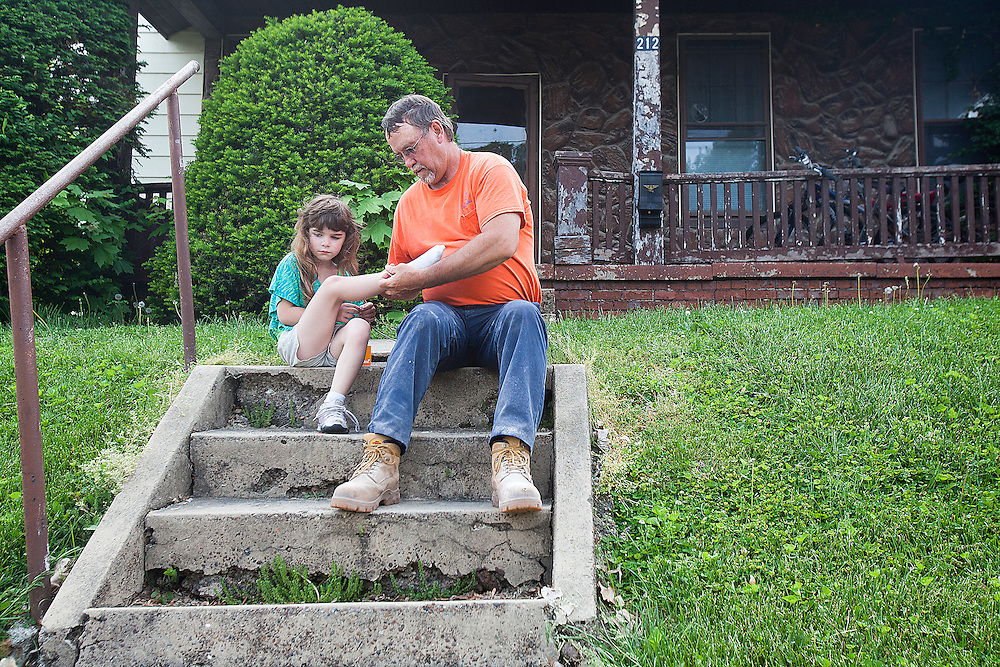 On the front porch steps of his Huntingburg home, Dale Payne helped Kiera Volz put her socks and shoes on so she could go to the park with her mother, Tara Volz, and half-sister Kayley Payne on May 8. Dale, who has known Kiera since she was born, has helped raise her since July 2010 and became her legal guardian in October 2011.
