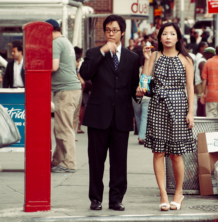 Asian couple waiting to cross street. NYC 2008