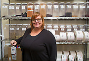 Emily Lawson with Pink House Alchemy stands next to herbs she uses to make her products in Fayetteville, Arkansas. Photo by Beth Hall