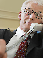 Business man using phone sitting on sofa close-up low angle view