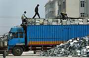 Workers unpack a truck-load of e-waste which has just arrived for processing in Guiyu.