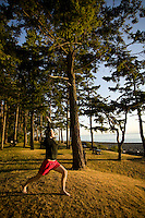 A woman greets the early morning sun during a yoga pose at Kitty Coleman Beach campground.  Courtenay, The Comox Valley, Vancouver Island, British Columbia, Canada.