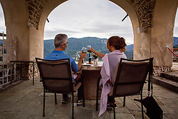 Couple siting and drinking wine on Bled castle. Photo by Ziga Zupan / Sportida
