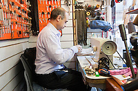 Side view of senior man working in a key shop
