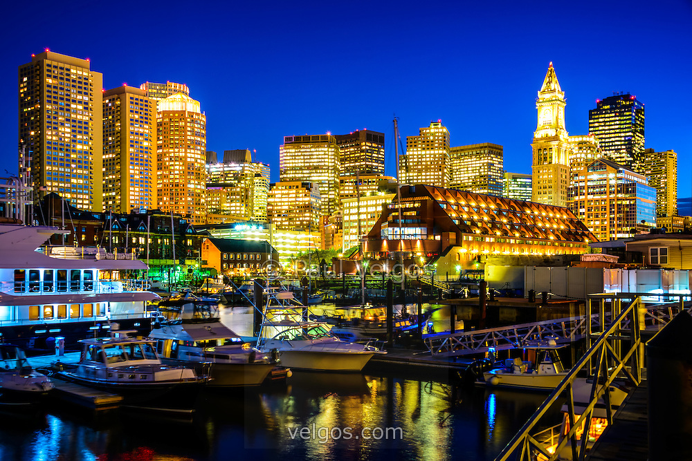 Boston skyline at night along the Boston Harbor waterfront with boats and downtown Boston buildings.