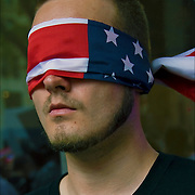 Conspiracy theory protester wearing an American flag (Blind Justice) as a mask  covering his eyes,near ground zero on 9-11-11.