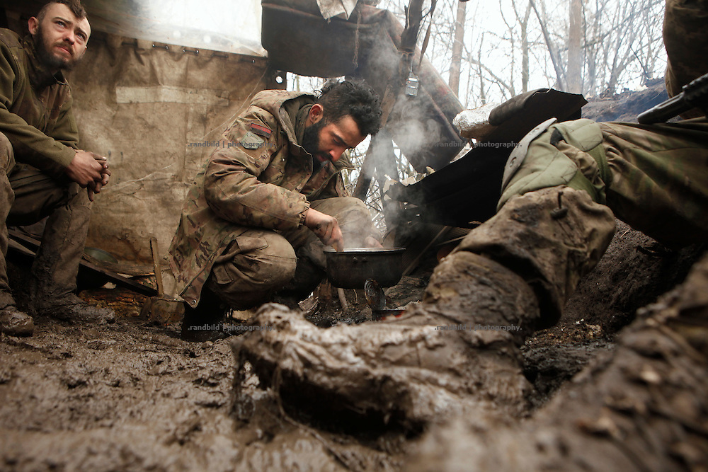 Ben (ce.) and Alex (le.) prepare a meal at the camp fire in the muddy trench at the donetsk frontline.<br />