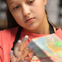 """Mary Margaret Deaton, 11, of Mooreville, keeps a close eye on her work as the paints the sides of her """"Chalk Paint Pour"""" project during Art/DIY Camp at Farmhouse Tuesday in Tupelo."""
