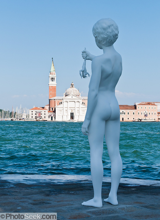 "In 2009, American sculptor Charles Ray (born 1953) installed ""Boy with Frog"" at the Punta della Dogana on Giudecca island, sestiere of Dorsoduro, Venice, Italy, Europe. The white eight-foot-tall sculpture depicts a boy holding a large frog above Giudecca Canal. Across the lagoon is Chiesa di San Giorgio Maggiore, a 16th century Benedictine church on the island of the same name. The basilica was designed in the classical renaissance style by Andrea Palladio and built from 1566-1610. The campanile (bell tower), first built in 1467, fell in 1774, and was rebuilt in neo-classic style by 1791. Venice (Venezia) is the capital of Italy's Veneto region, named for the ancient Veneti people from the 10th century BC. The romantic ""City of Canals"" stretches across 117 small islands in the marshy Venetian Lagoon along the Adriatic Sea Europe."