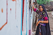 A gujarati girl posting in front of her house in a village in Bhuj