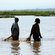 Women wade out to floating reefs of water hyacinth to catch mud fish. Mud fish, used for bait, have appeared in Lake Victoria for the first time because of the water hyacinth infestation. Pollution of the lake is causing water hyacinth to grow out of control and is a sign of the environmental problems affecting the lake.