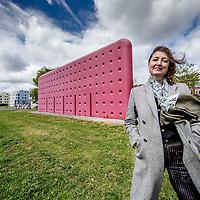 Nederland, Amsterdam, 15 mei 2016.<br /> Esther Eikelenboom over het kunstwerk De Muur van haar vader Alfred Eikelenboom (1936-2014).<br /> Het kunstwerk staat op een grasveldje tussen de Meeuwenlaan en de Gedempte Insteekhaven in Noord. Het is een grote rode muur.<br /> <br /> Foto: Jean-Pierre Jans