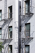Traditional typical metal fire escape ladder on walk-up brownstone apartment block on west side Manhattan, New York City