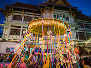 25 NOVEMBER 2015 - BANGKOK, THAILAND:  People donate money to the temple during Loy Krathong at Wat Yannawa in Bangkok. Loy Krathong takes place on the evening of the full moon of the 12th month in the traditional Thai lunar calendar. In the western calendar this usually falls in November. Loy means 'to float', while krathong refers to the usually lotus-shaped container which floats on the water. Traditional krathongs are made of the layers of the trunk of a banana tree or a spider lily plant. Now, many people use krathongs of baked bread which disintegrate in the water and feed the fish. A krathong is decorated with elaborately folded banana leaves, incense sticks, and a candle. A small coin is sometimes included as an offering to the river spirits. On the night of the full moon, Thais launch their krathong on a river, canal or a pond, making a wish as they do so.    PHOTO BY JACK KURTZ