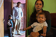 Roma family in their home in the all-Roma village of Unguraia in Botosani County, Romania. The mother sits with the youngest child on her lap inside one of the rooms while the father and a son stand in the hallway outside. They have three more children, all of them girls.