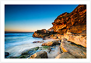 The first morning sunlight brings out brilliant colours on the sandstone cliffs. [Tamarama, Sydney, NSW, Australia].<br />