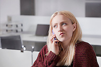 Thoughtful young businesswoman using cell phone at office