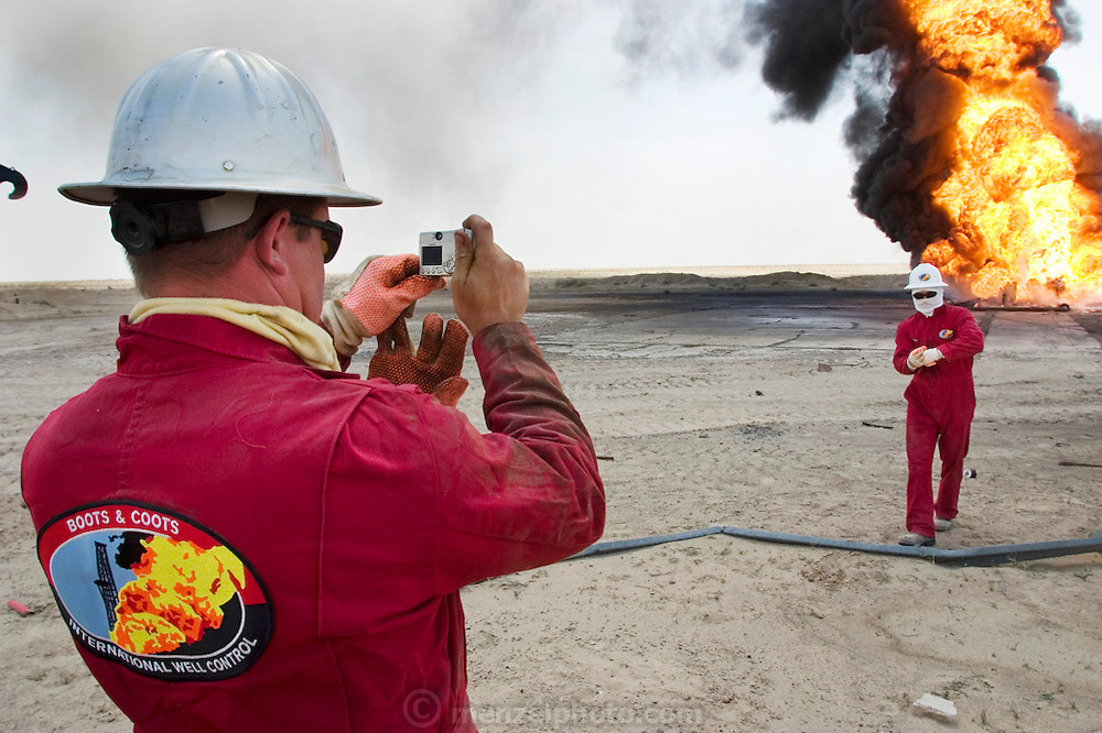 Boots and Coots firefighters photograph each other near a raging oil well fire in Rumaila field, Southern Iraq. The Rumaila field is one of Iraq's biggest with five billion barrels in reserve. Boots and Coots had a team of firefighters in Kuwait ready to go into Iraq several weeks before the war began. All of their equipment (including bulldozers and trucks) was flown in from Texas on large Russian cargo planes (AN-124s). Many of the wells are 10,000 feet deep and produce huge volumes of oil and gas under tremendous pressure, which makes capping them very difficult and dangerous. Rumaila is also spelled Rumeilah.
