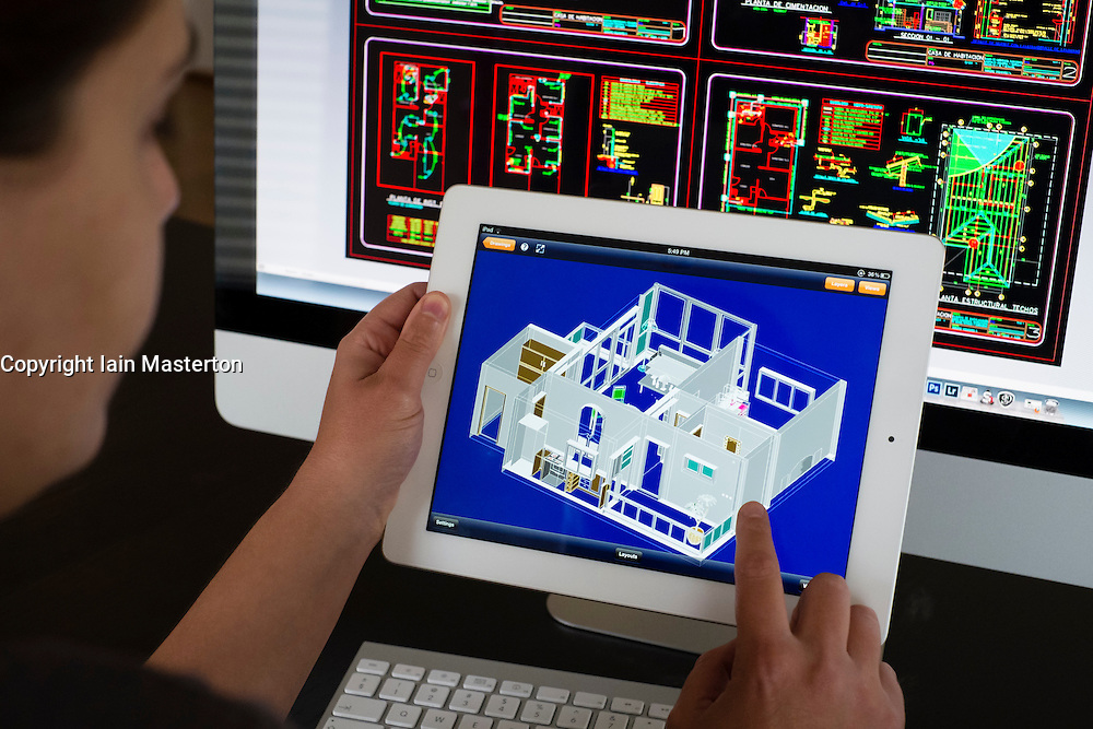 Architect using iPad 3D CAD Computer Aided design application to model 3D layout design of new house