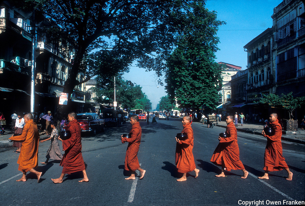 Buddhist monks cross the street on their way to receive offerings of food, in Rangoon (Yangon), Myanmar (Burma)<br /> Photo by Owen Franken