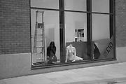 Woman working in shop front window alongside headless mannequin.