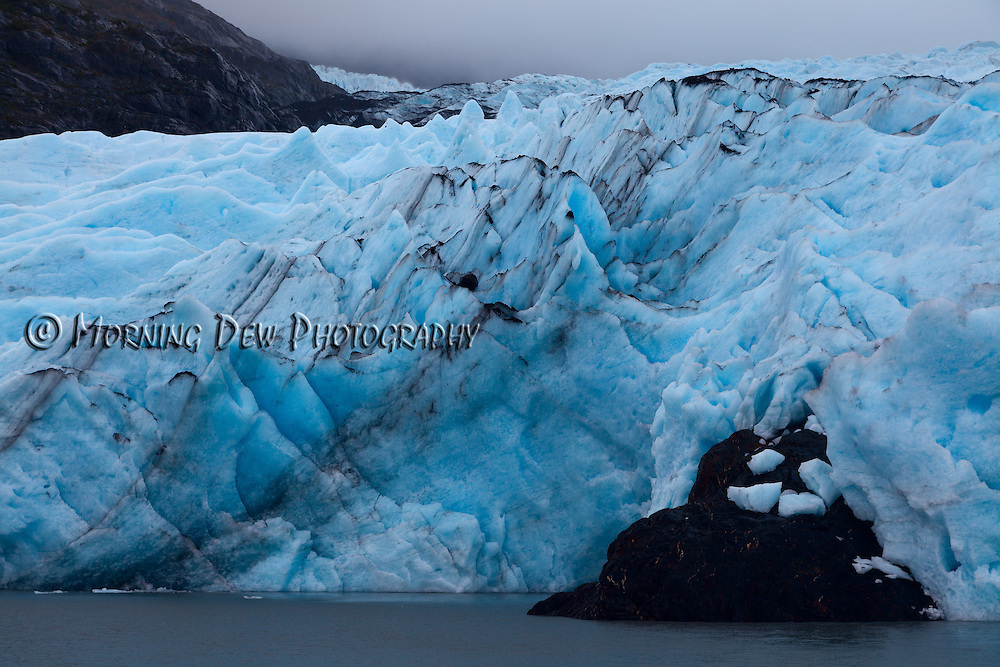 Pinacles of blue ice march towards the water. Portage Glacier, Alaska