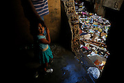 A child holding the hand of a man stands next to a mountain of rubbish inside the <br /> IBGE abandoned building in Rio de Janeiro, Brazil, May 2, 2015. Photo/Pilar Olivares