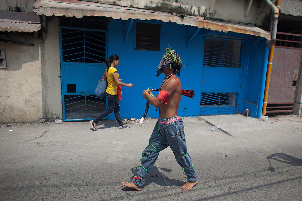 A hooded penitent walking through street during flagellation ritual to atone for their sins in observance of Holy Week Thursday, April 5, 2012 at Los Angeles city, Philippines. Such practice is rejected by the Catholic church.