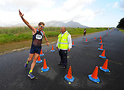 CAPE TOWN, SOUTH AFRICA - OCTOBER 10: Marc Mundell spreads his arms as he makes his turn in front of walk official, Gavin Burgess, during the South African Race Walking Championship at Youngsfield Military Base on October 10, 2015 in Cape Town, South Africa. (Photo by Roger Sedres/ImageSA)