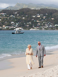 The Prince of Wales and the Duchess of Cornwall walk along the Grand Anse beach during a one day visit to the Caribbean island of Grenada.