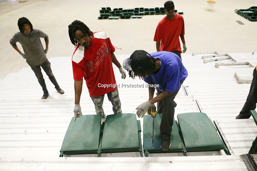 VanNess Riley, from left, Timothy Gathings, Jonathan Lambert, and Jermaine Crump work on unscrewing and carrying away sets of seats as they work on removing the lower bowl at the BancorpSouth Arena Tuesday morning.