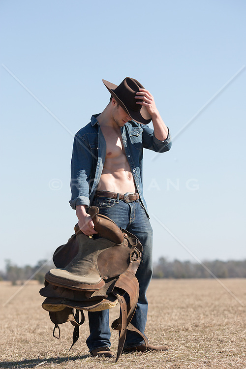 hot cowboy with an open shirt walking on a ranch with a saddle in his hand