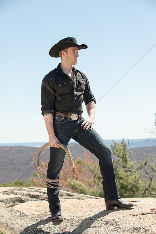 rugged masculine cowboy on top of a mountain