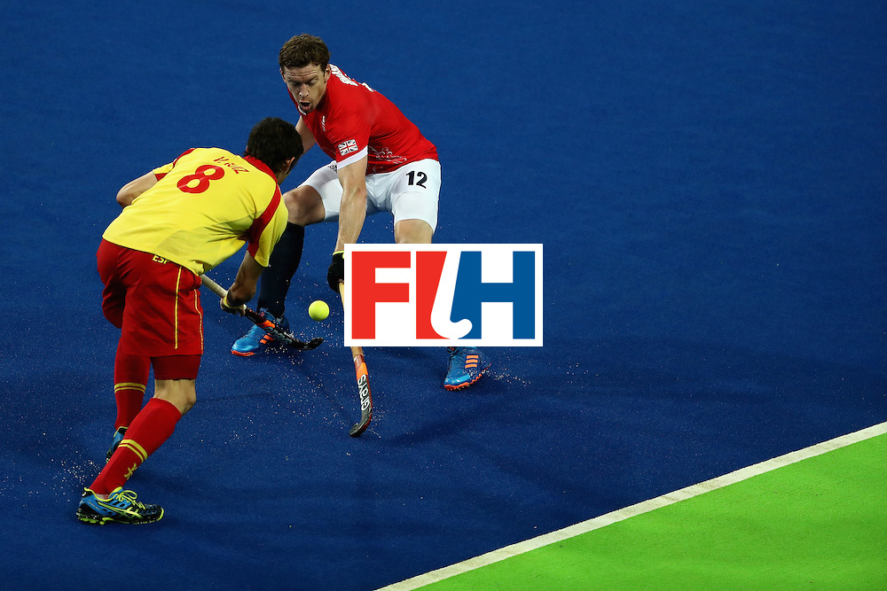 RIO DE JANEIRO, BRAZIL - AUGUST 12:  Michael Hoare #12 of Great Britain defends Vicenc Ruiz #8 of Spain during a Men's Preliminary Pool B match on Day 7 of the Rio 2016 Olympic Games at the Olympic Hockey Centre on August 12, 2016 in Rio de Janeiro, Brazil.  (Photo by Sean M. Haffey/Getty Images)